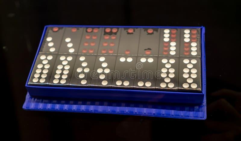 Domino nell'imballaggio di plastica blu sul fondo nero fotografie stock libere da diritti