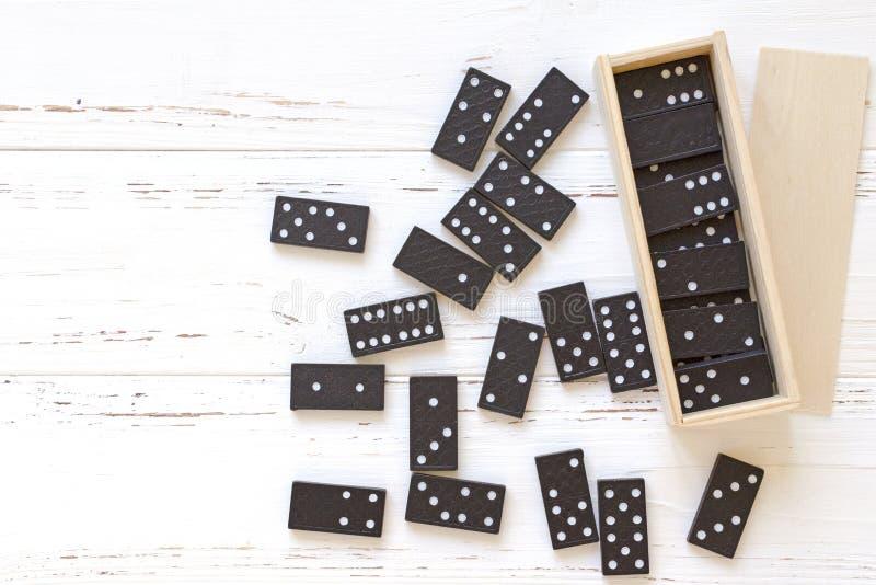 Domino neri sulla tavola d'annata di legno bianca fotografie stock