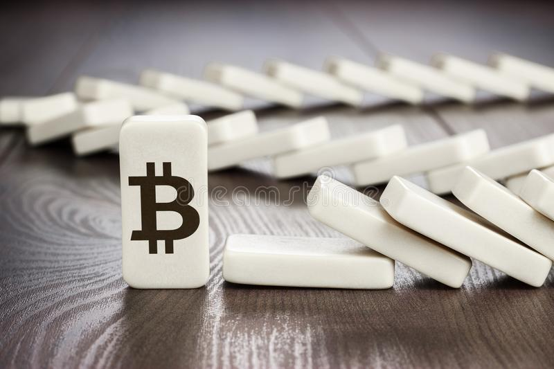 Domino piece with bitcoin symbol standing still while others fell down. bitcoin cryptocurrency sustainability concept stock images