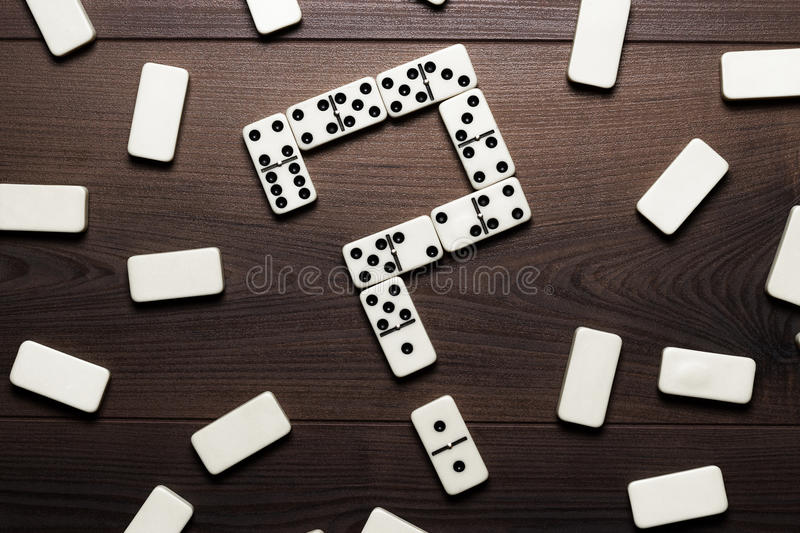 Domino pieces forming question mark on wooden stock photo