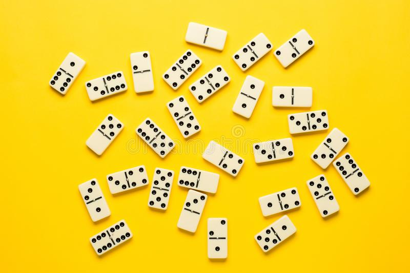 Domino pieces over bright yellow background, top view. Flat lay background. royalty free stock photo