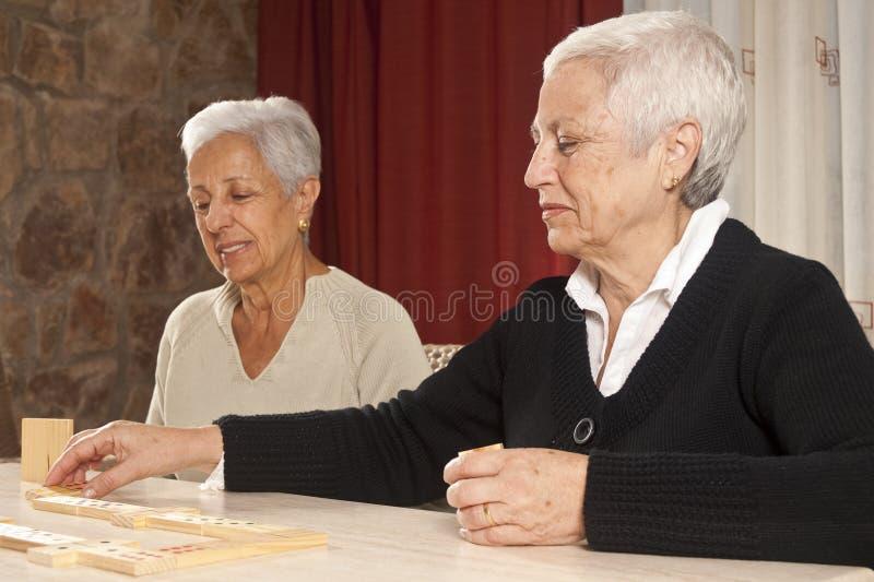 domino som leker kvinnor för pensionär två arkivfoton