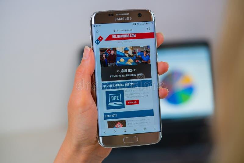 Dominobrickapizzawebbplats på mobiltelefonen royaltyfri bild