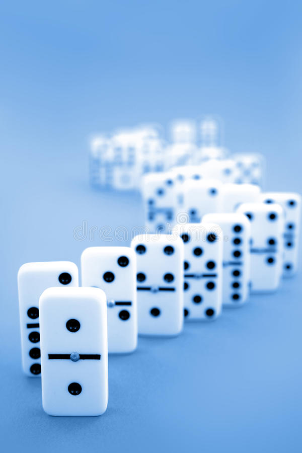 Dominoes. Standing on blue background stock images