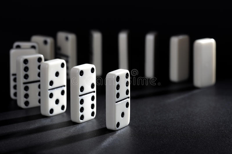 Dominoes. Lined up ready to fall concept for domino effect, balance and risk royalty free stock photos