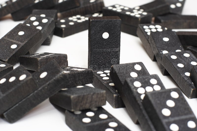 Dominoes. A lone domino remains standing after the rest have fallen like... dominoes stock images