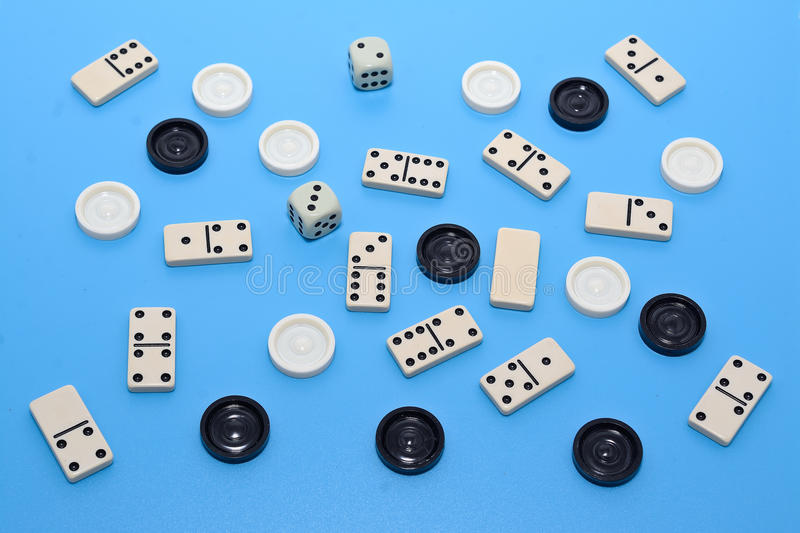 Dominoes and checkers on blue background stock photography