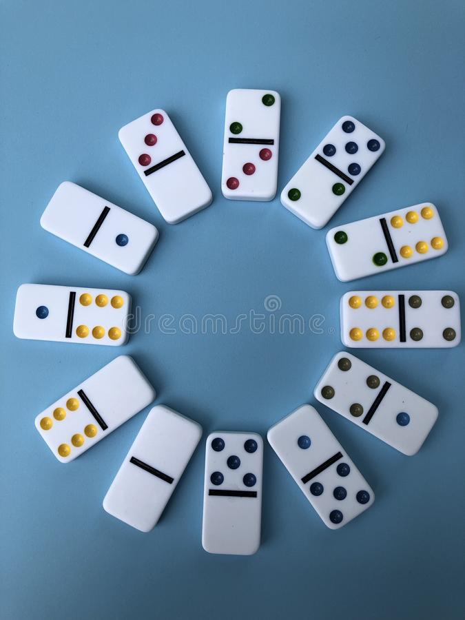Dominoes in a circle. Several color coded dominoes displayed on a blue background in a circular fashion royalty free stock photo