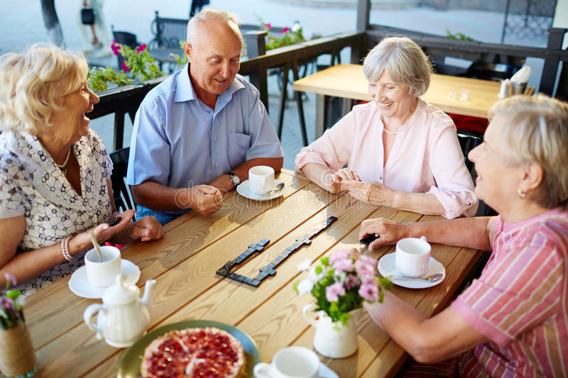 Dominoes players. Happy senior friends playing dominoes at leisure stock image