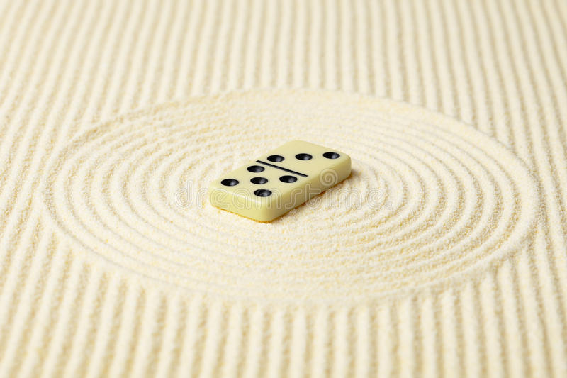 Dominoes on surface of yellow sand royalty free stock photos