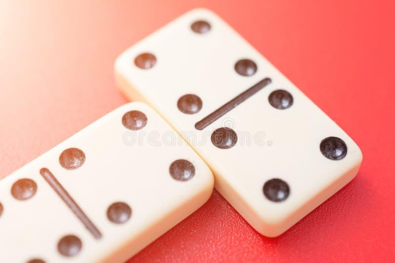 Dominos auf roter Tabelle lizenzfreie stockbilder