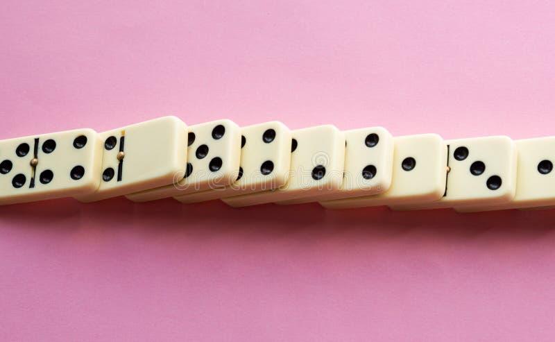 Dominos détruits sur le rose photographie stock