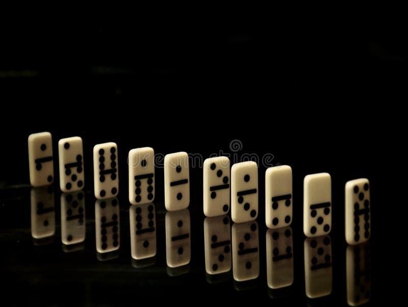 Dominos sur un fond noir image libre de droits