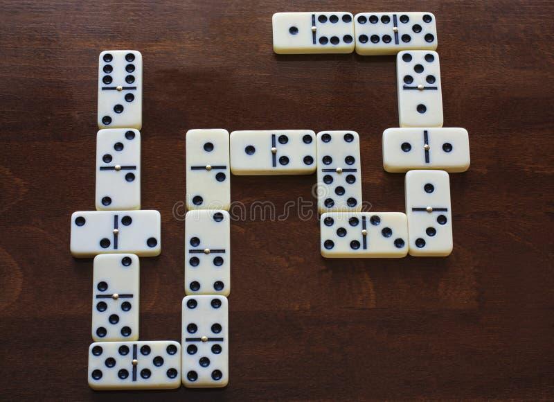 Dominostücke auf dem braunen Holztischhintergrund lizenzfreie stockbilder