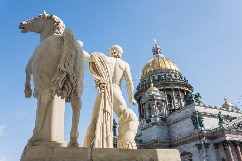 Domkyrka för St Isaacs, i förgrunden en skulptur av en manlig krigare med en häst i St Petersburg arkivbild