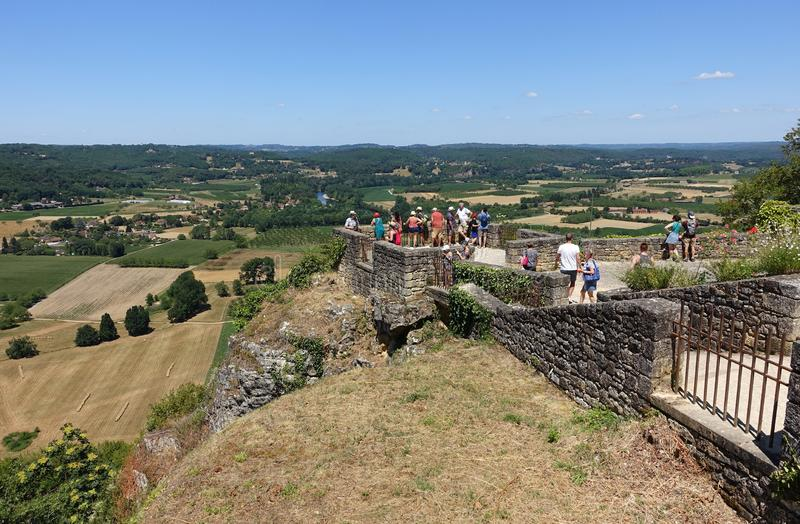 Tourists standing on a viewing platform. Domme, France 15 July 2019: Tourists standing on a viewing platform overlooking the Dordogne from the town of Domme in stock photography