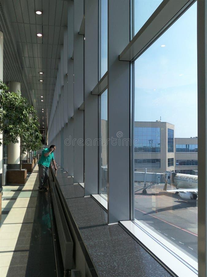 Domodedovo, Rússia 8 de junho de 2019: um homem está em uma janela na construção do aeroporto de Domodedovo e na fala em um telef imagens de stock royalty free