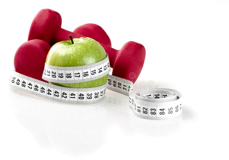 Domoren met het meten van band en appel voor dieet stock afbeelding