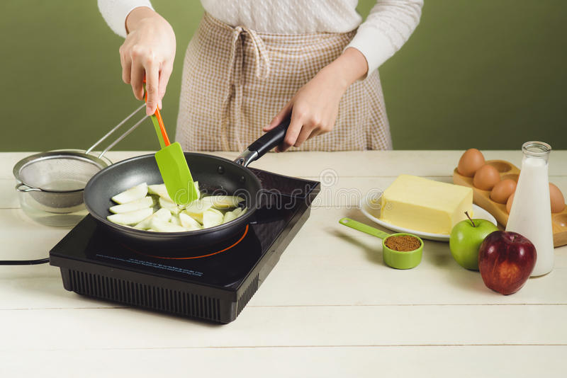 Domowa żona jest ubranym fartucha robić Kroki robić kulinarnemu jabłczanemu tortowi obraz royalty free