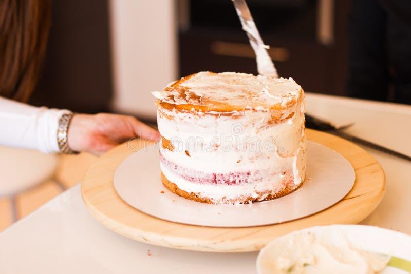 Domowa żona jest ubranym fartucha robi ostatnim szlifom na urodzinowym deserowym czekoladowym torcie Kobieta robi domowej roboty  fotografia stock