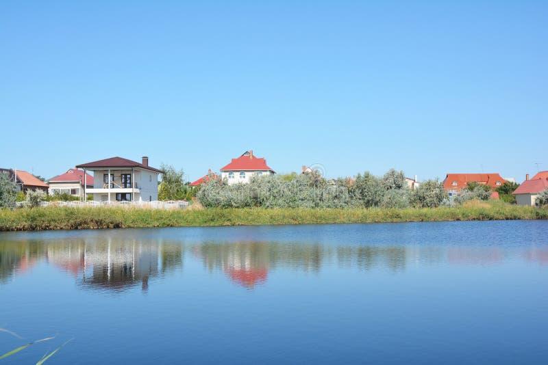 Domowa budowa z dużo domy i chałupy na jeziornym banku z pięknym widokiem zdjęcie royalty free