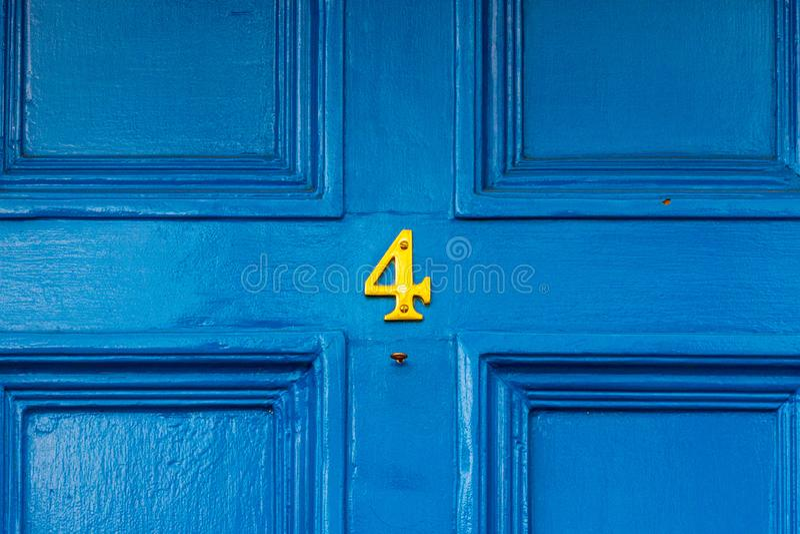 Domowa liczba cztery z cztery w brązie na błękitnym drewnianym drzwi zdjęcie royalty free