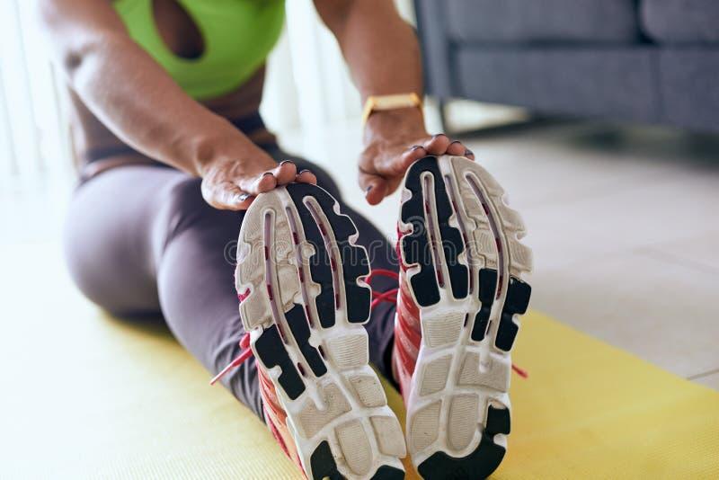Domowa sprawności fizycznej murzynka Robi treningu rozciąganiu Na ochraniaczu zdjęcia royalty free