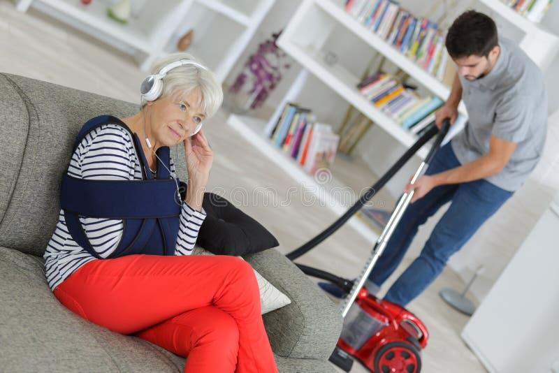 Domowej pomocy mężczyzna cleaning ladys próżniowy mieszkanie zdjęcia stock