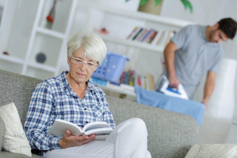 Domowej pomocy mężczyzna prasowanie i starszej damy czytelnicza książka zdjęcie stock