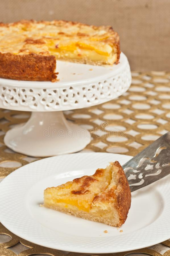 Domowej roboty, świeżo piec klin śliwkowy custard tarta ono ślizga się z srebnego porcja klinu na round, bielu talerz fotografia stock