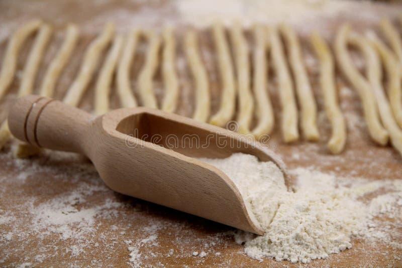 Domowej roboty świeży uncooked Włoski makaronu fusilli z mąką na drewnianym tle fotografia royalty free