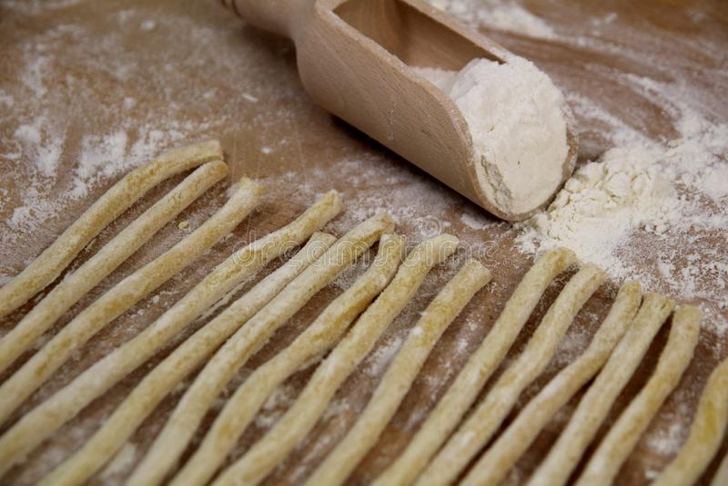 Domowej roboty świeży uncooked Włoski makaronu fusilli z mąką na drewnianym tle zdjęcie royalty free