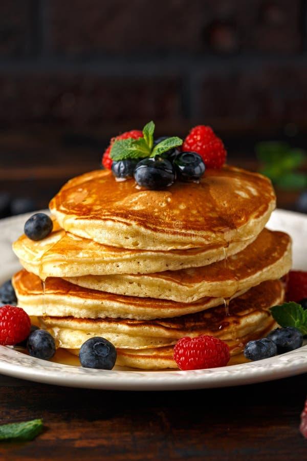 Domowej roboty amerykańscy bliny z świeżą czarną jagodą, malinkami i miodem, Zdrowego ranku wieśniaka śniadaniowy styl zdjęcia stock