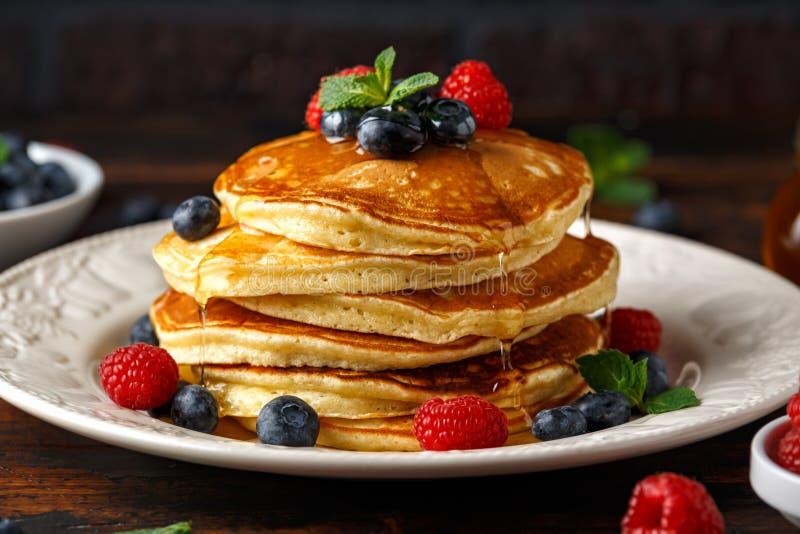 Domowej roboty amerykańscy bliny z świeżą czarną jagodą, malinkami i miodem, Zdrowego ranku wieśniaka śniadaniowy styl obrazy royalty free