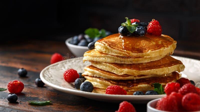 Domowej roboty amerykańscy bliny z świeżą czarną jagodą, malinkami i miodem, Zdrowego ranku wieśniaka śniadaniowy styl zdjęcia royalty free