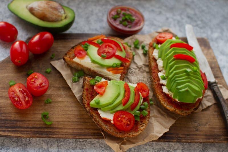 domowej roboty avocado grzanki na żyto chlebie, pomidorach, scallions, pieprzu i kremowym serze, fotografia stock