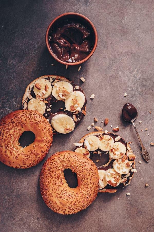 Domowej roboty bagels z czekoladową śmietanką, bananem i dokrętkami na ciemnym nieociosanym tle, Wyśmienicie słodki śniadaniowy O zdjęcia royalty free