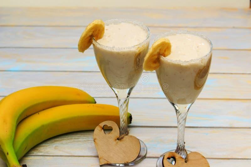 Domowej roboty Bananowi smoothies na drewno stole w dwa szkłach obraz stock