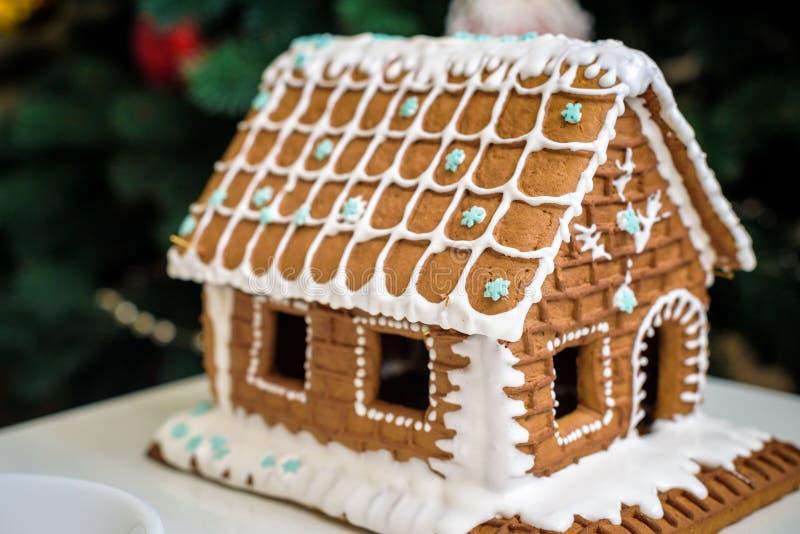 Domowej roboty Bożenarodzeniowy Piernikowy dom w śniegu Dekorująca choinka w tle zdjęcie stock