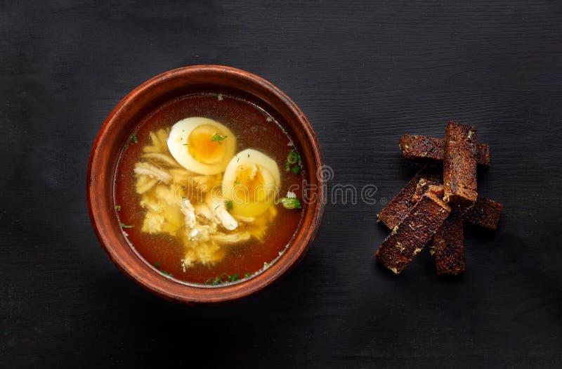 Domowej roboty bouillon lub rosół z kurczaka mięsem, jajko w glina talerzu zdjęcia stock