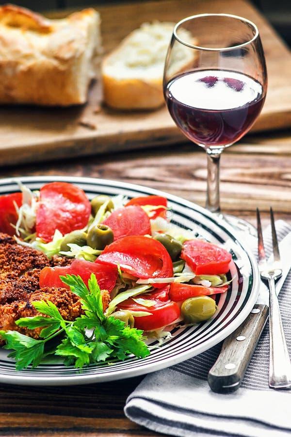 Domowej roboty Breaded niemiec Weiner Schnitzel i świeżego warzywa wiosny sałatka z pomidorem, zielonymi oliwkami, kapustą i piet obraz royalty free