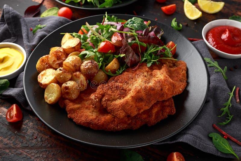 Domowej roboty breaded wieprzowiny schnitzel z pieczon? grul? i warzywami zdjęcie royalty free