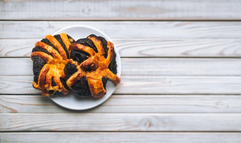 Domowej roboty ciasta z makowymi ziarnami na spodeczku Drewniany backgroun obraz royalty free