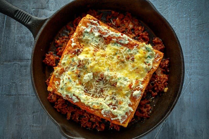 Domowej roboty Crispy lasagna w żelaznej niecce z minced wołowina bolognese kumberlandem, parmesan ser fotografia stock