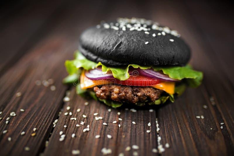 Domowej roboty Czarny hamburger z serem Cheeseburger z czarną babeczką o fotografia stock