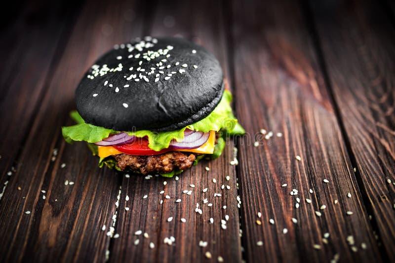 Domowej roboty Czarny hamburger z serem Cheeseburger z czarną babeczką na ciemnym drewnianym tle obraz royalty free