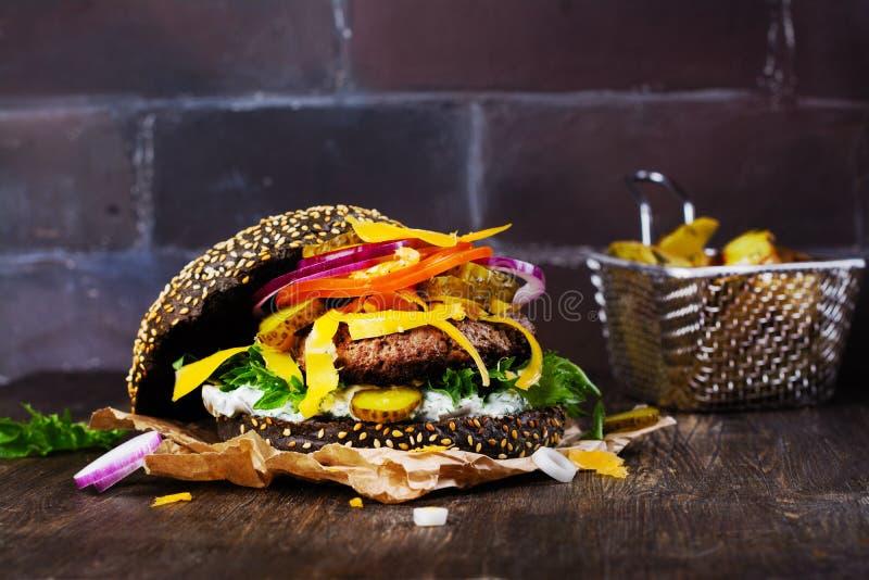 Domowej roboty czarny hamburger z tzatziki kumberlandem, tartym serem i mięsnym kitem, Piec grula ketchup i kliny obrazy royalty free
