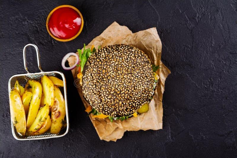 Domowej roboty czarny hamburger z tzatziki kumberlandem, tartym serem i mięsnym kitem, Piec grula ketchup i kliny obraz royalty free