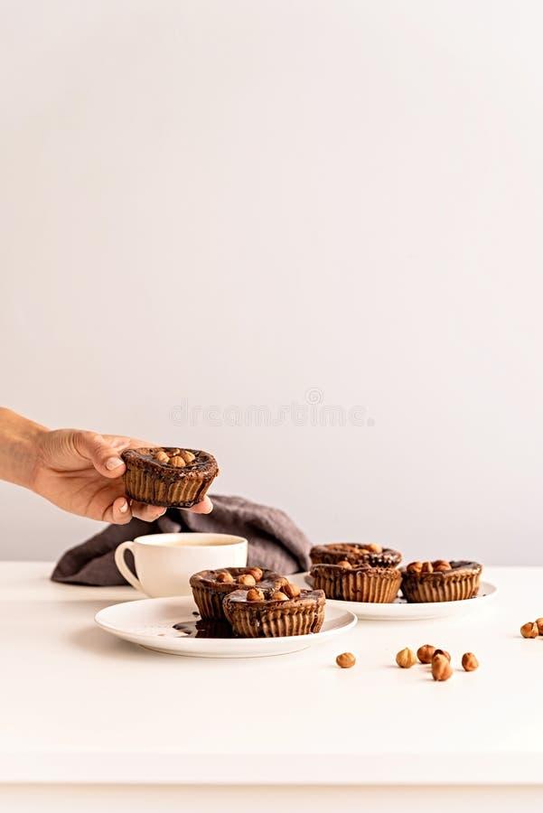 Domowej roboty czekoladowe babeczki z glazurowaniem, orzechami włoskimi i filiżanka kawy na bielu stołu frontowym widoku, obraz stock
