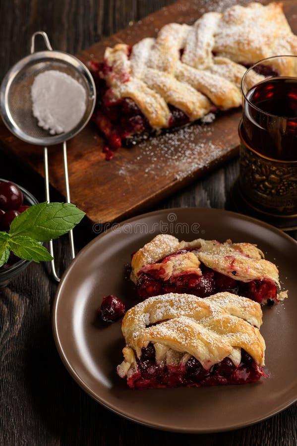 Domowej roboty czereśniowy ptysiowego ciasta warkocz na błękitnym drewnianym tle, fotografia stock